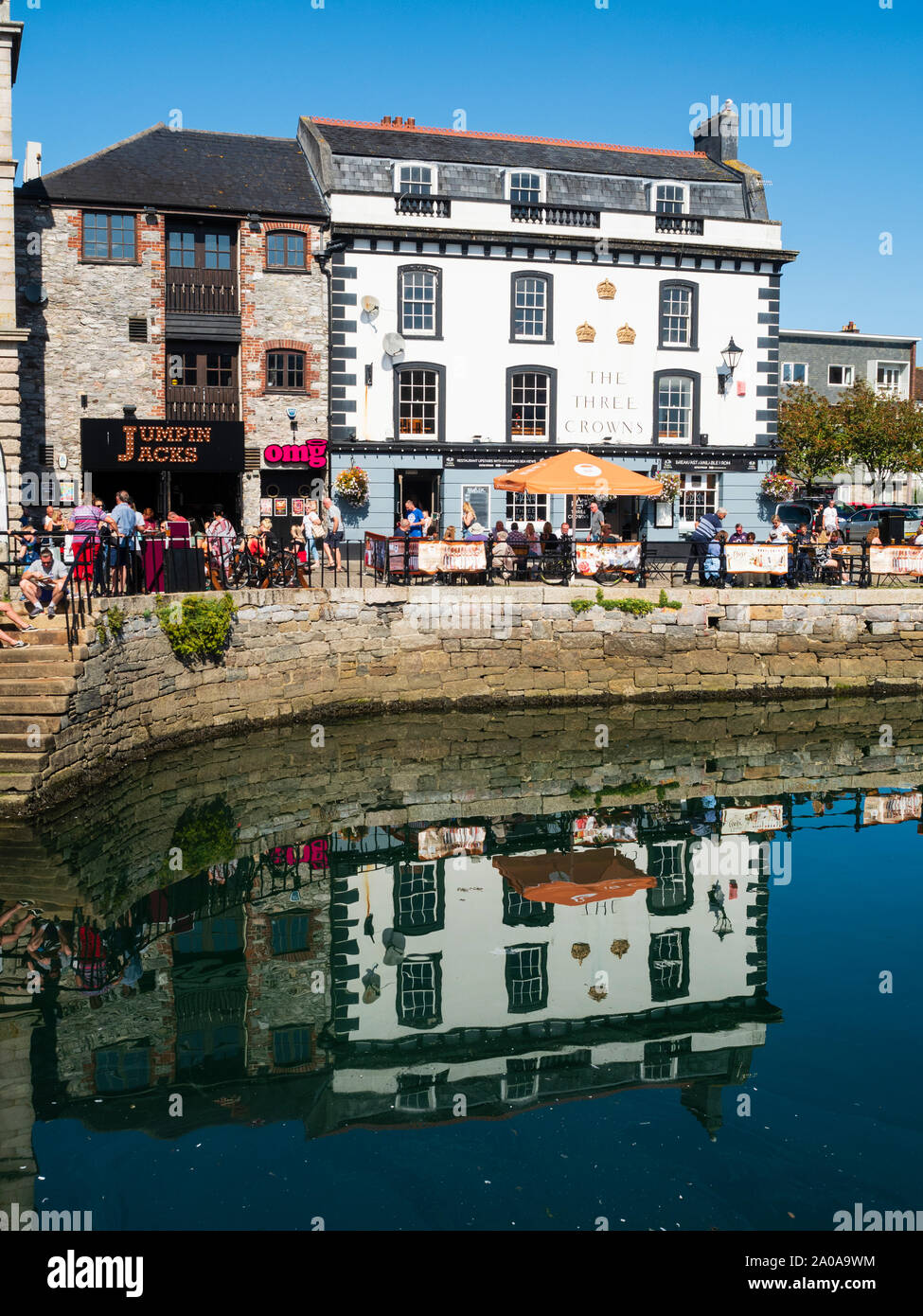 diners-at-tables-outside-the-three-crowns-pub-reflected-in-the-water-of-sutton-harbour-plymouth-2A0A9WM.jpg