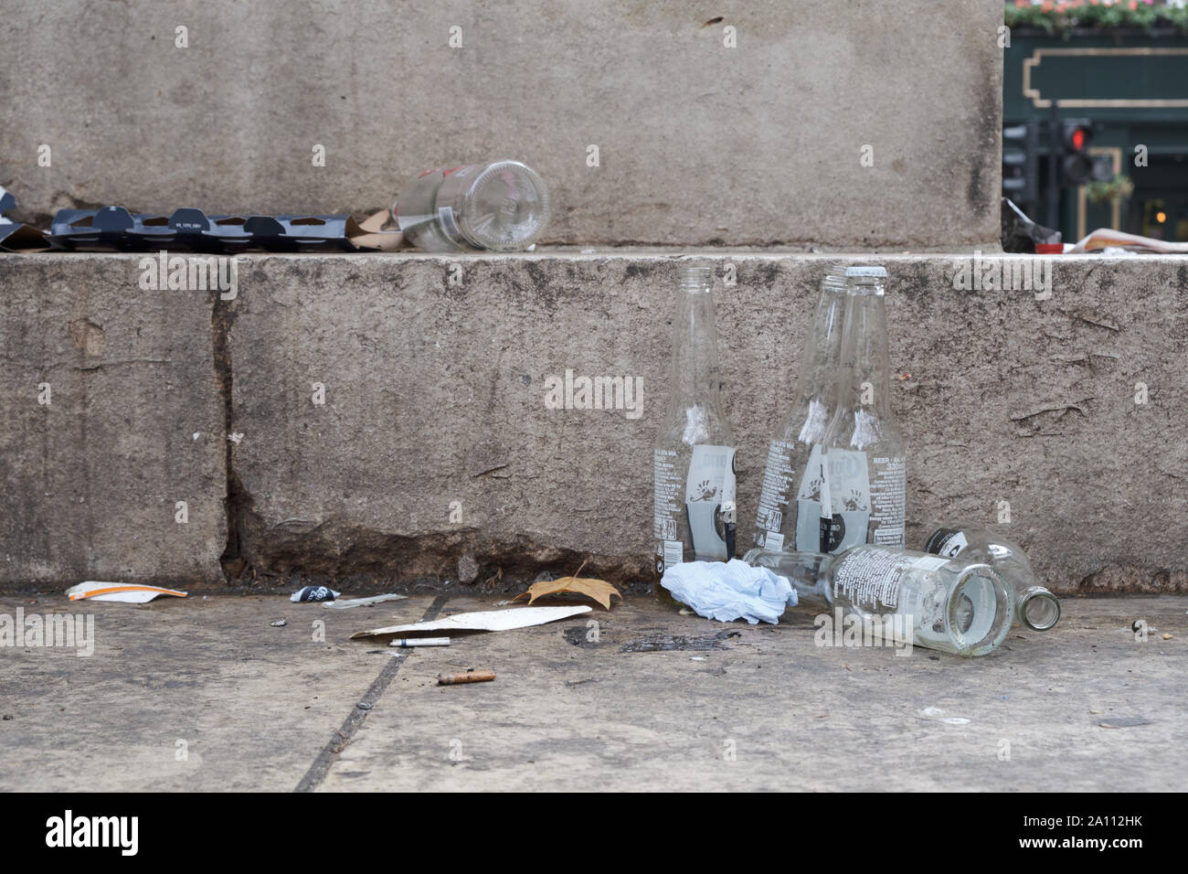 Empty bottles of beer and liquor left abandoned  at foot of nameless monument in London Stock Photo