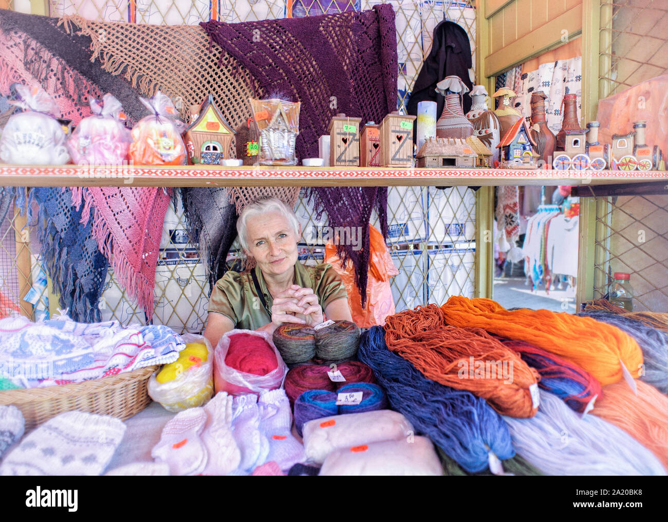 environmental-portrait-of-beautiful-shopkeeper-in-the-marketplace-tallinn-estonia-with-souvenirs-wool-and-woolen-goods-for-sale-european-travel-and-2A20BK8.jpg