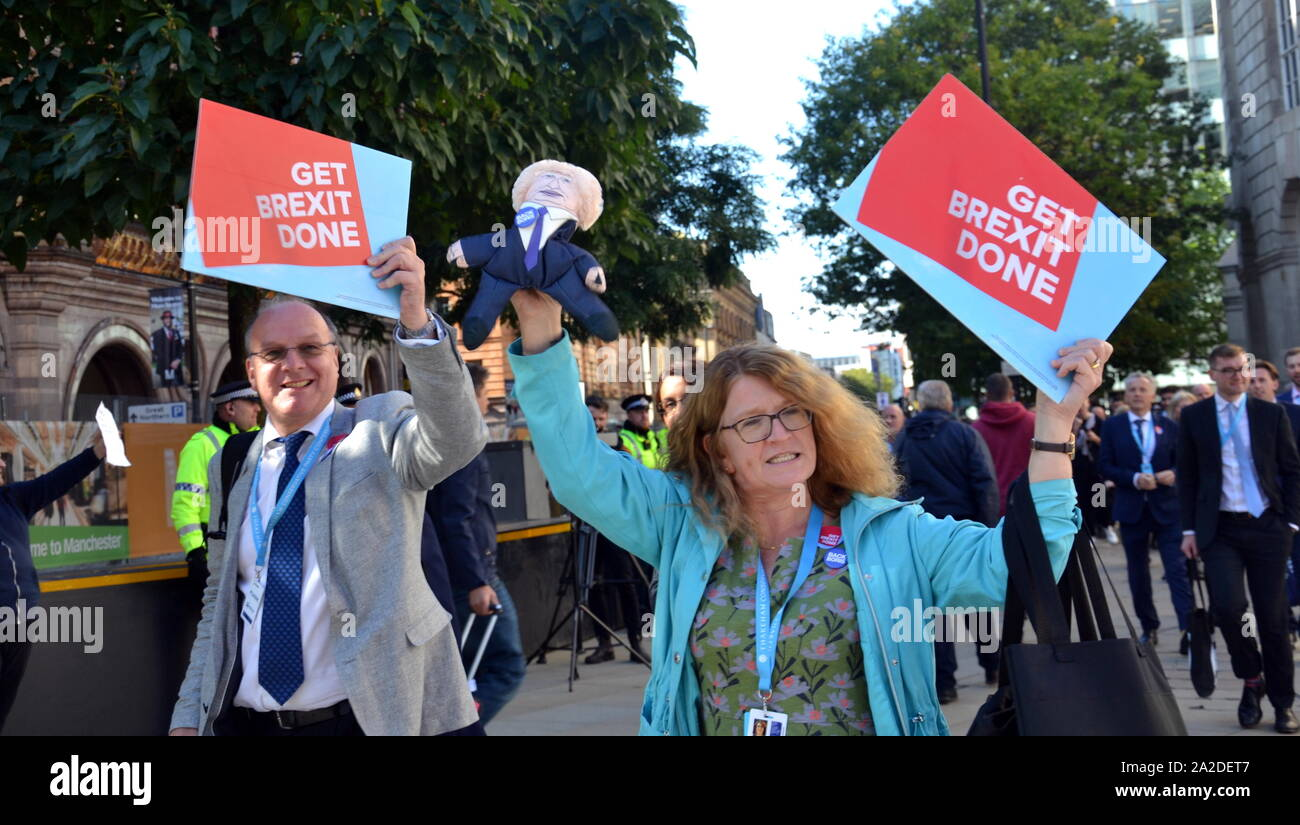 Conference delegates leaving the Conservative Party Conference in Manchester, uk, on the final day carry 'Get Brexit Done' signs, a major theme of the conference, and a Boris Johnson doll, past protesters. Stock Photo