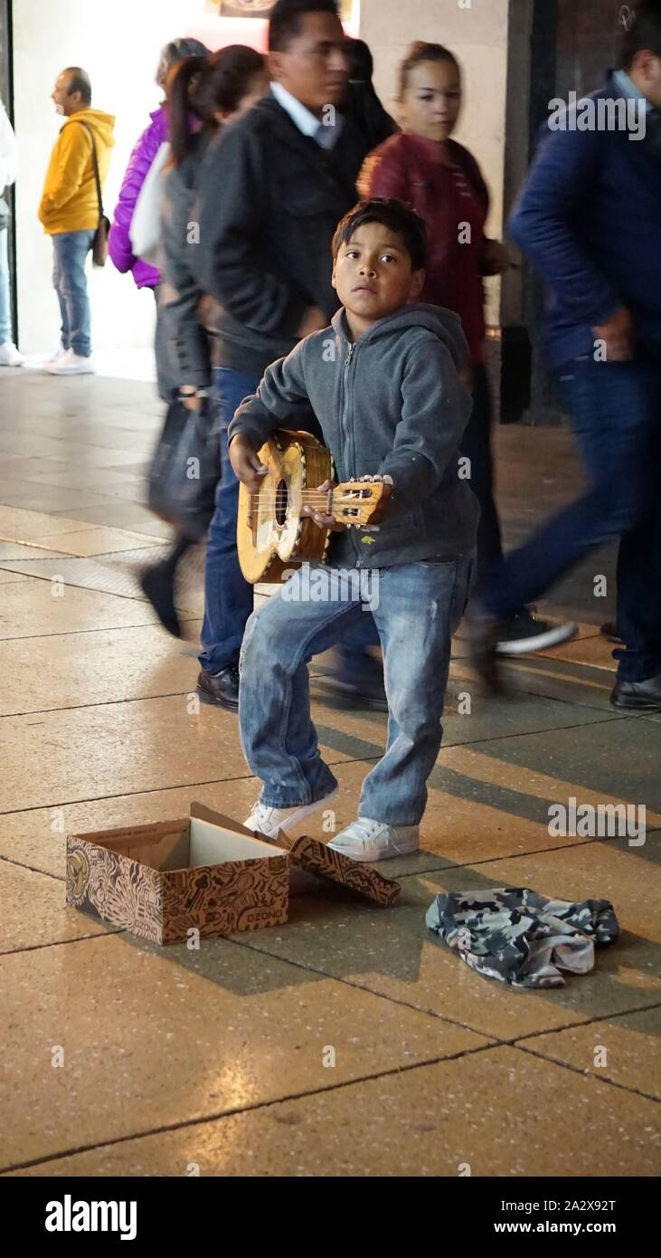 boy-playing-guitar-on-street-for-money-with-pedestrians-behind-him-on-ave-5-de-mayo-centro-historico-mexico-city-mexico-2A2X92T.jpg