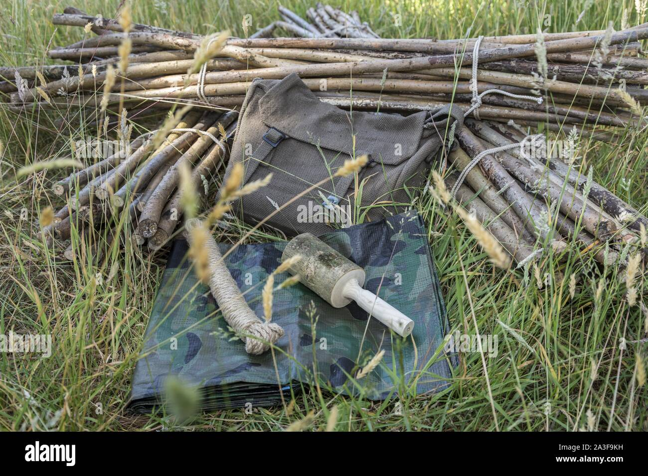 Equipment for making a basic tent,sticks,mallet,rope,tarpaulin. Stock Photo