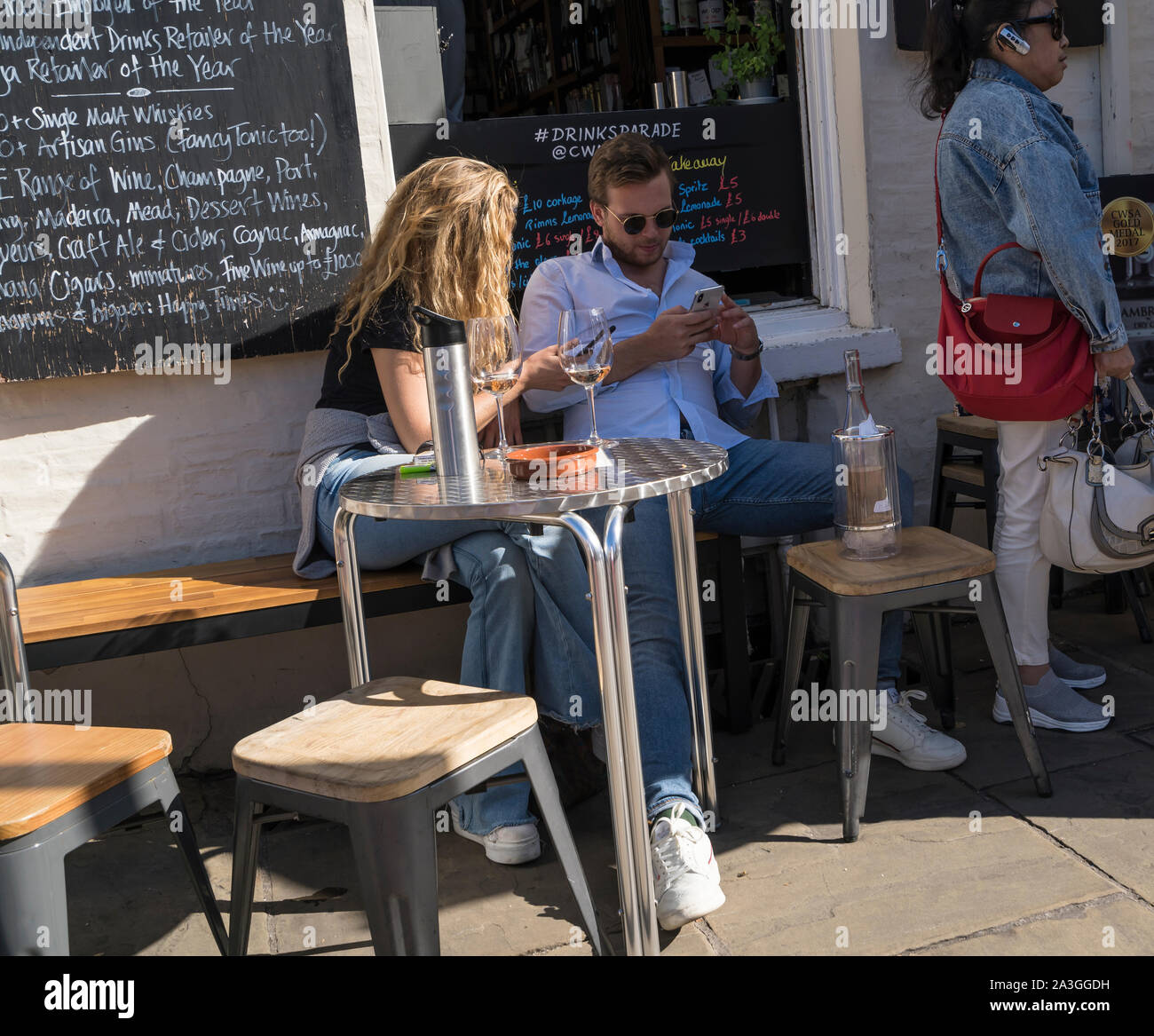 Man and woman sat at table with bottle and glasses having drinks Cambridge City 2019 Stock Photo