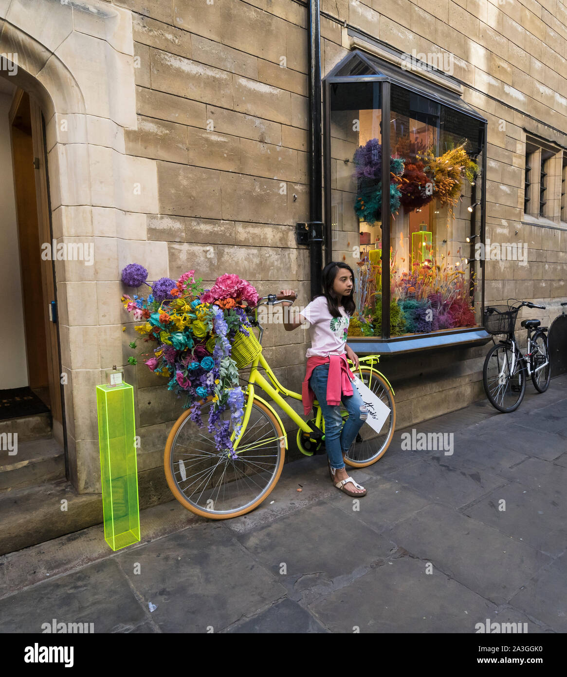 Young girl posing for photo by advertisement bike Cambridge 2019 Stock Photo