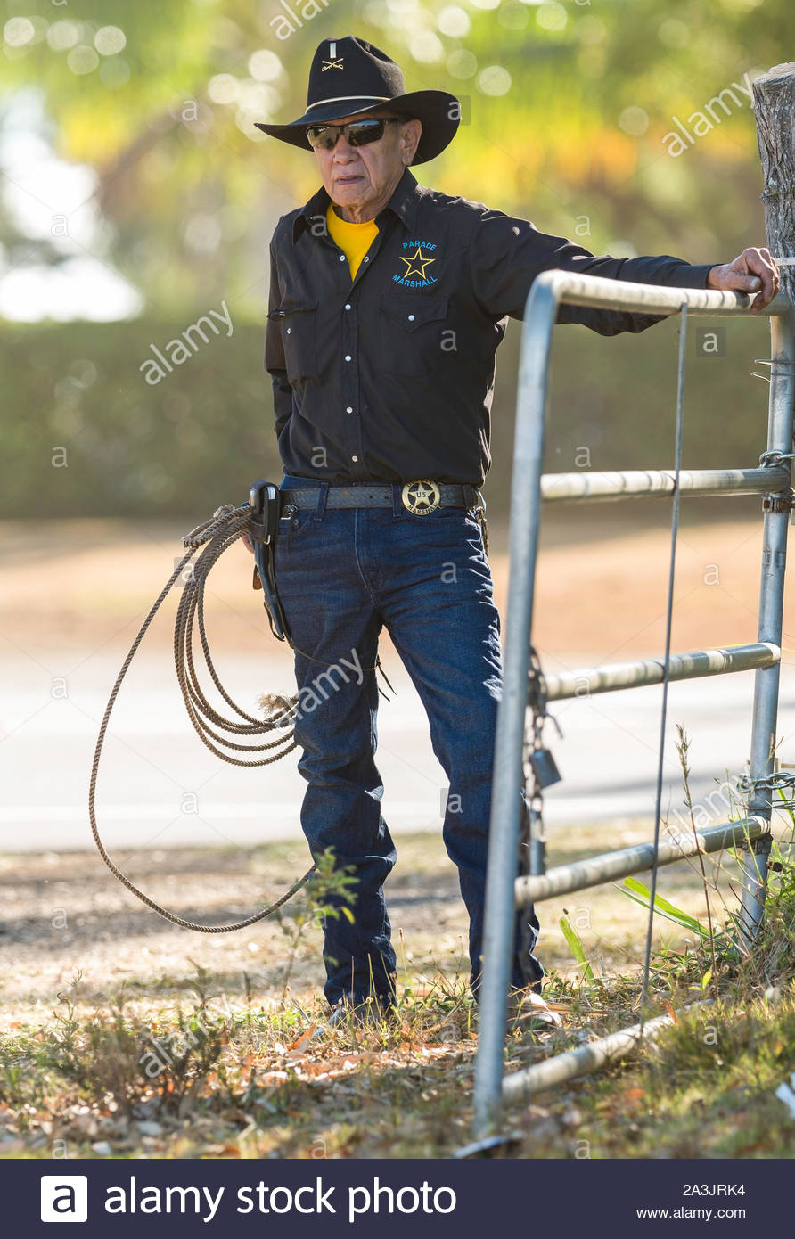 Mature man dressed in a black long sleeve shirt, black cowboy hat and jeans holding a coiled lasso at gate Stock Photo