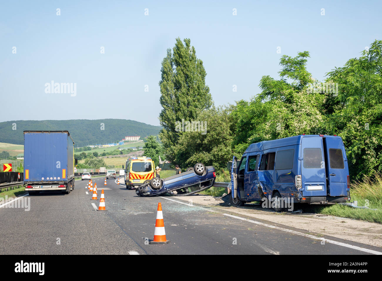 Car crash accident on highway. Damaged blue minibus after collision, overturned car and ambulance car on roadside. Traffic cones at accident site - Stock Image