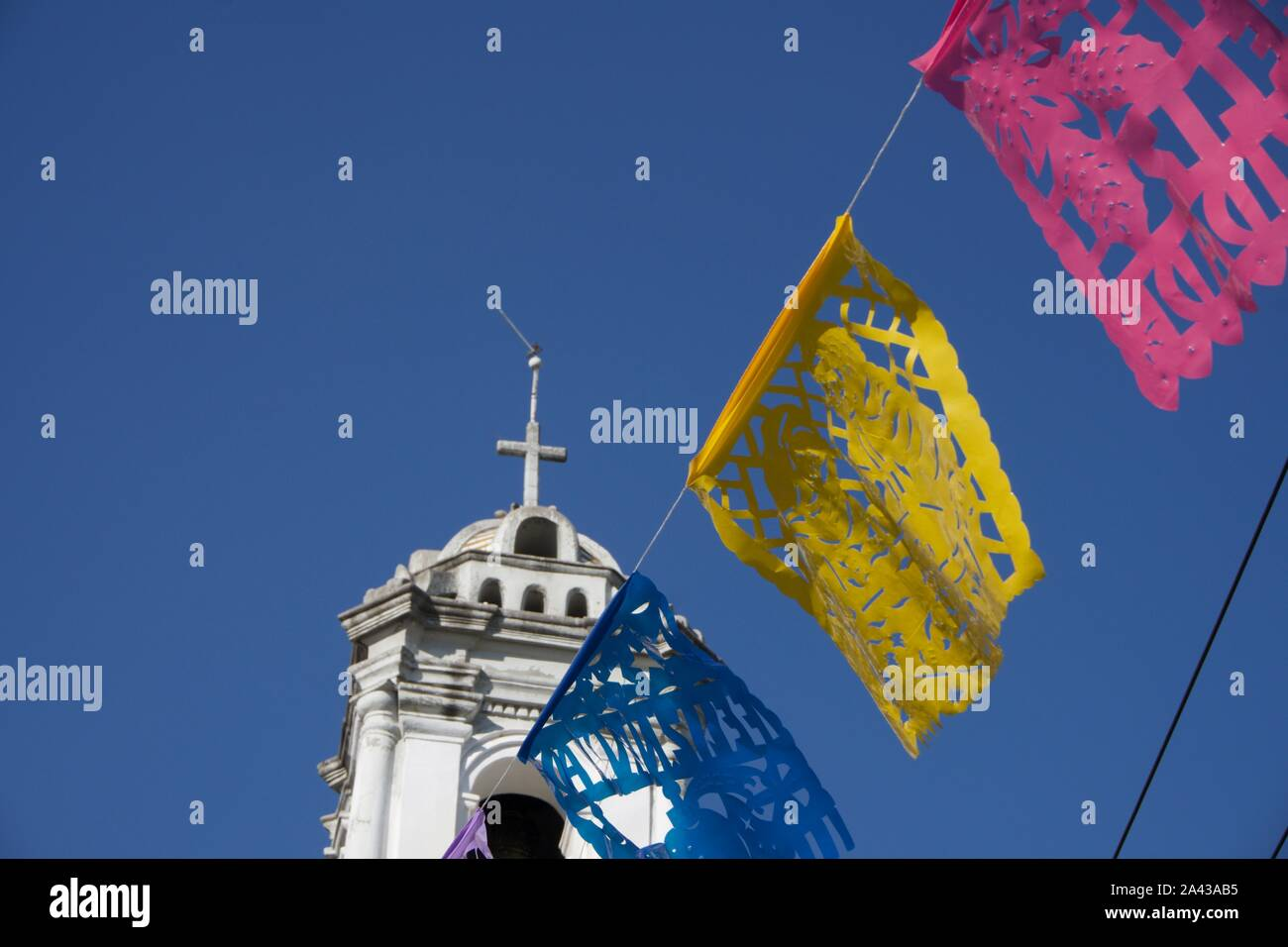La iglesia de Santa Ana, Church of Santa Ana, barrio de Peralvillo, Cuauhtémoc. Papel picado (cut paper flags) and bell tower with cross. Mexico City. Stock Photo