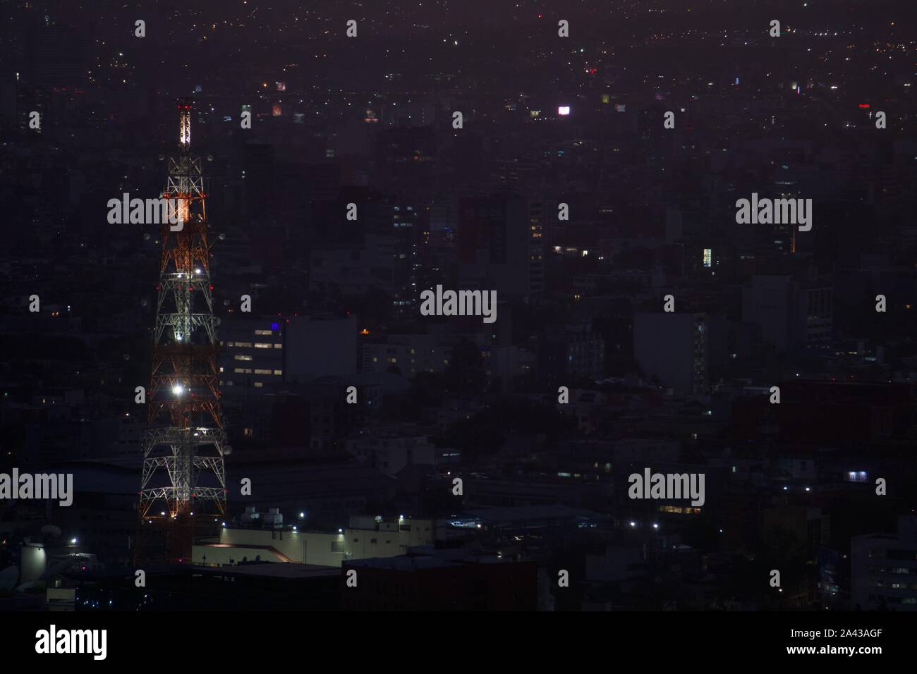 Vintage red and white radio tower at night, backed by city lights and urban density. Mexico City, Mexico. Stock Photo