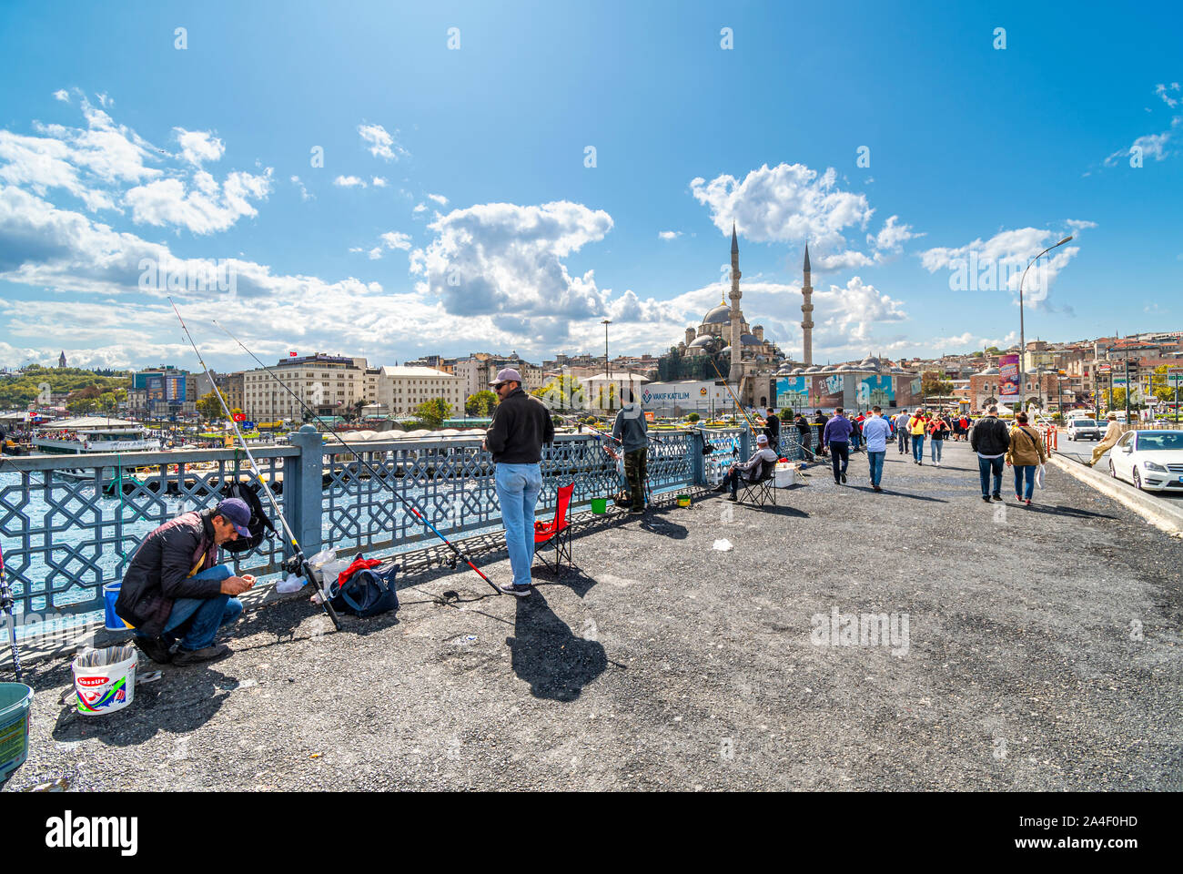 Local Turkish fishermen hang their fishing poles off the Bosphorus Bridge, with the Sultanahmet district and Suleymaniye Mosque in the distance. Stock Photo