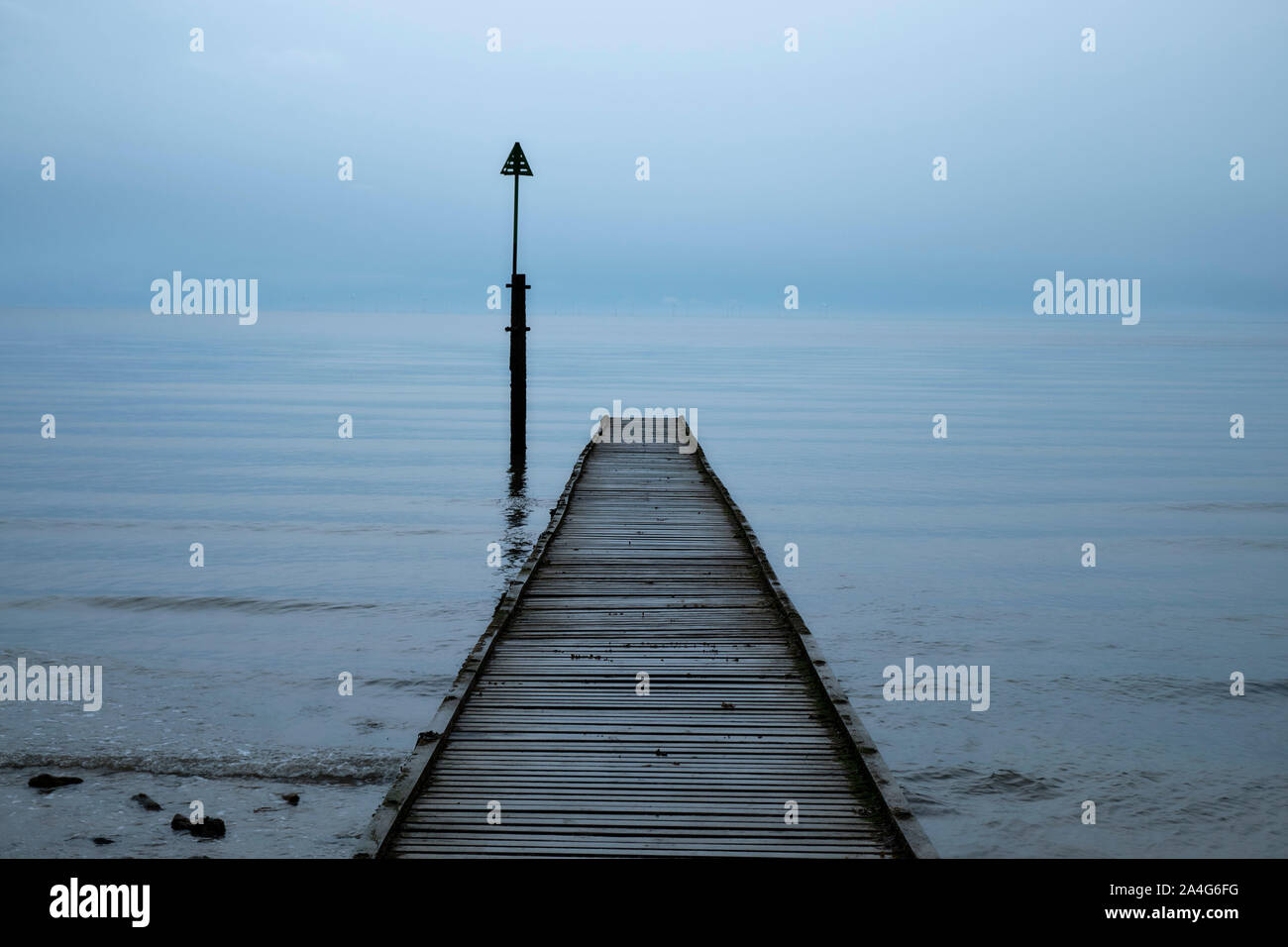 old-wooden-single-pier-leading-into-a-foggy-ocean-with-little-variation-from-sky-to-water-2A4G6FG.jpg