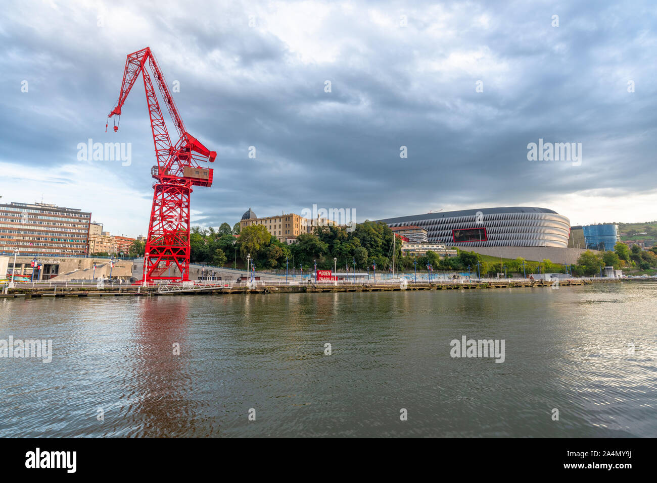 15/09-19, Bilbao, Spain. The crane, named La Carola, is a left over from the areas industrial past. The San Mamés soccer stadium, home to Athletic Bil Stock Photo