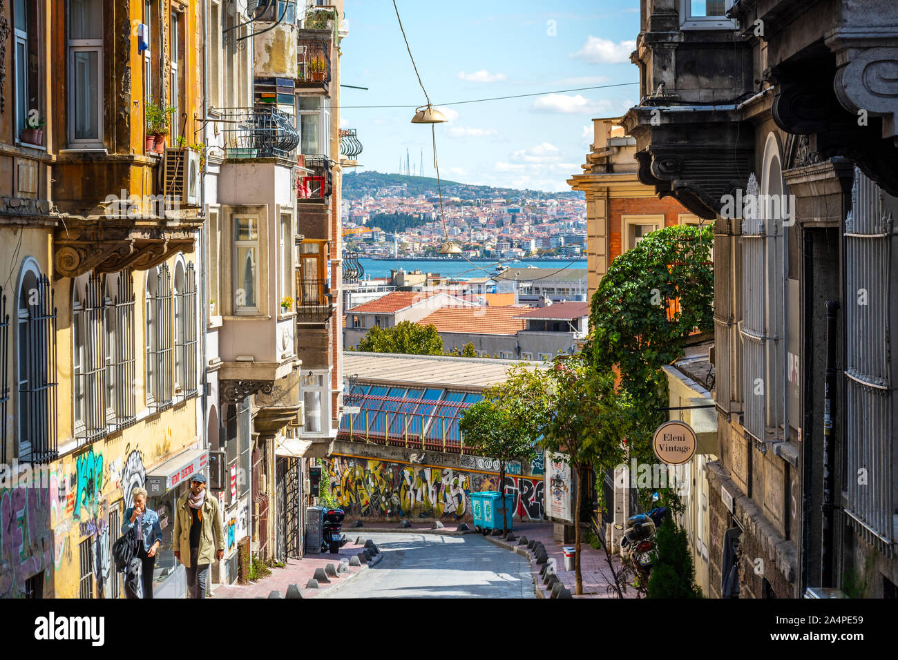 A couple walks the hilly Galata Karakoy district with the Bosphorus River, Asia and Golden Horn in the distance in Istanbul, Turkey. Stock Photo