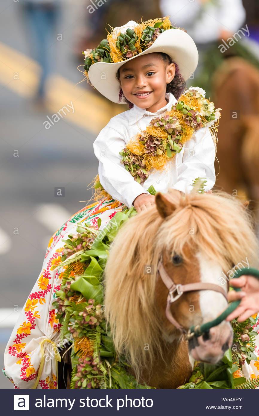 Young girl dressed as a Hawaiian Pa'u rider being led on a pony up Baldwin Avenue during the 54th annual Makawao Rodeo Parade, Makawao, Maui, Hawaii Stock Photo