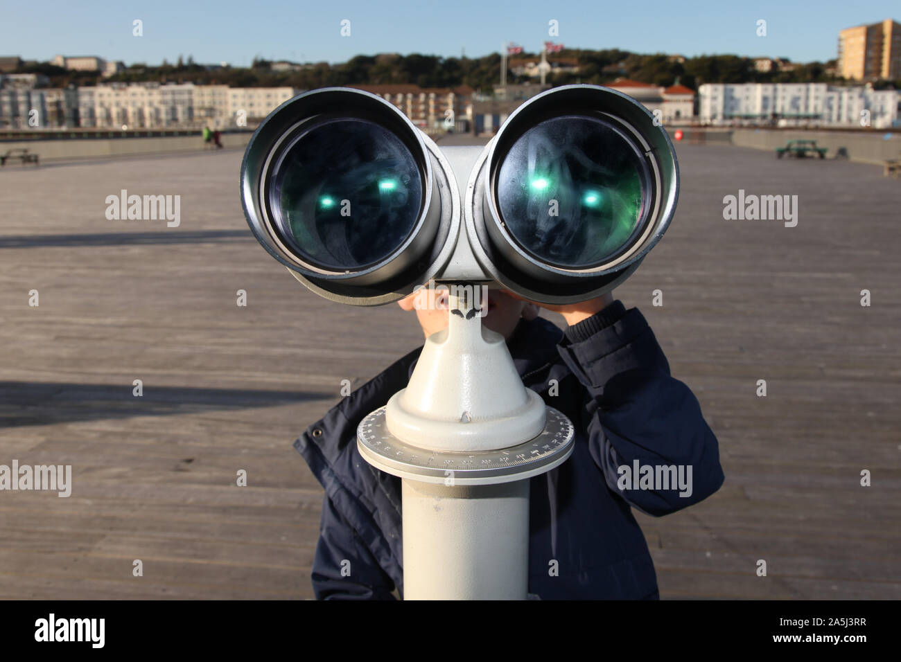 Young child looking through public binoculars looking out on Hastings pier in daytime Stock Photo