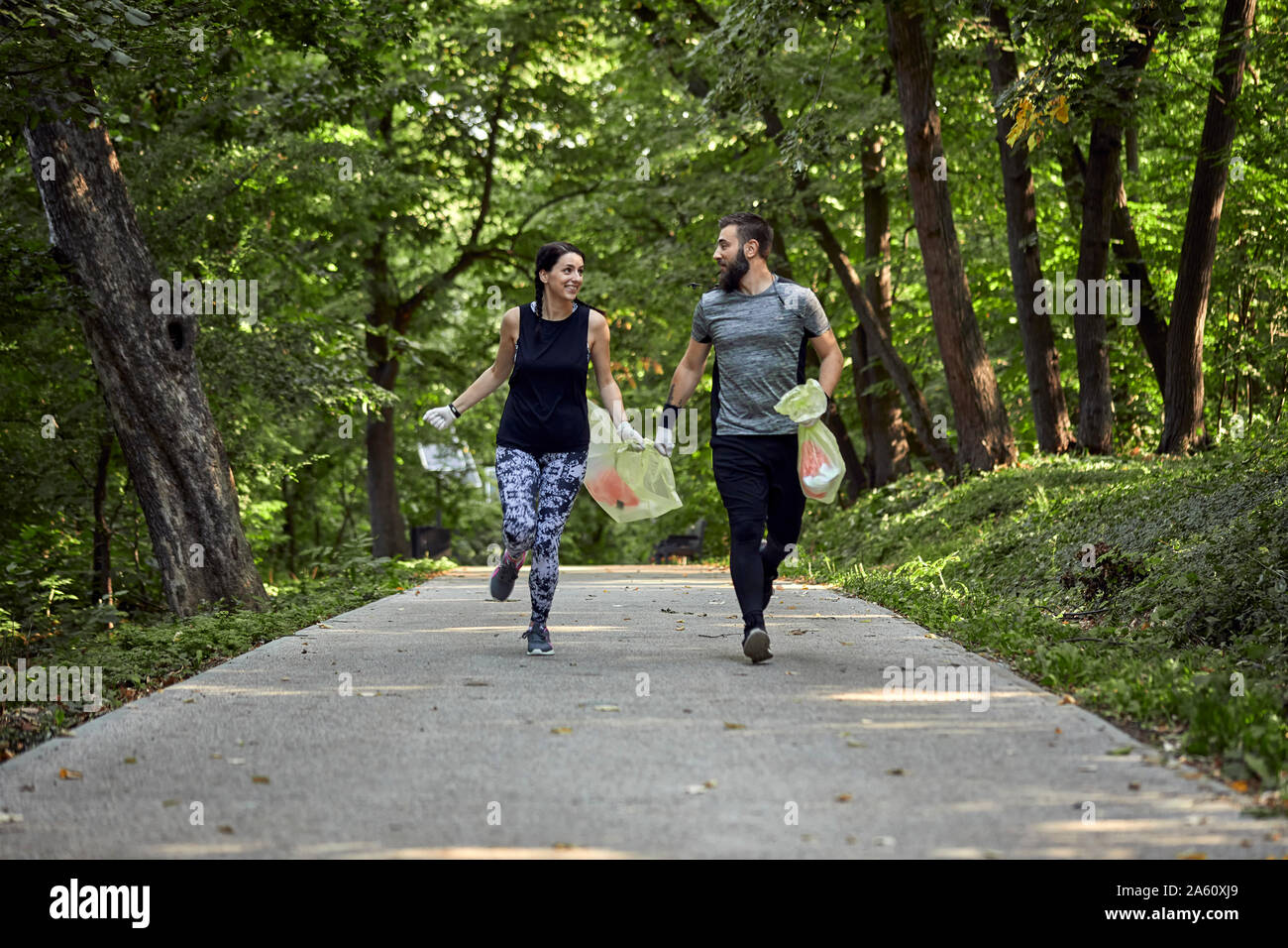 Couple plogging on forest path Stock Photo