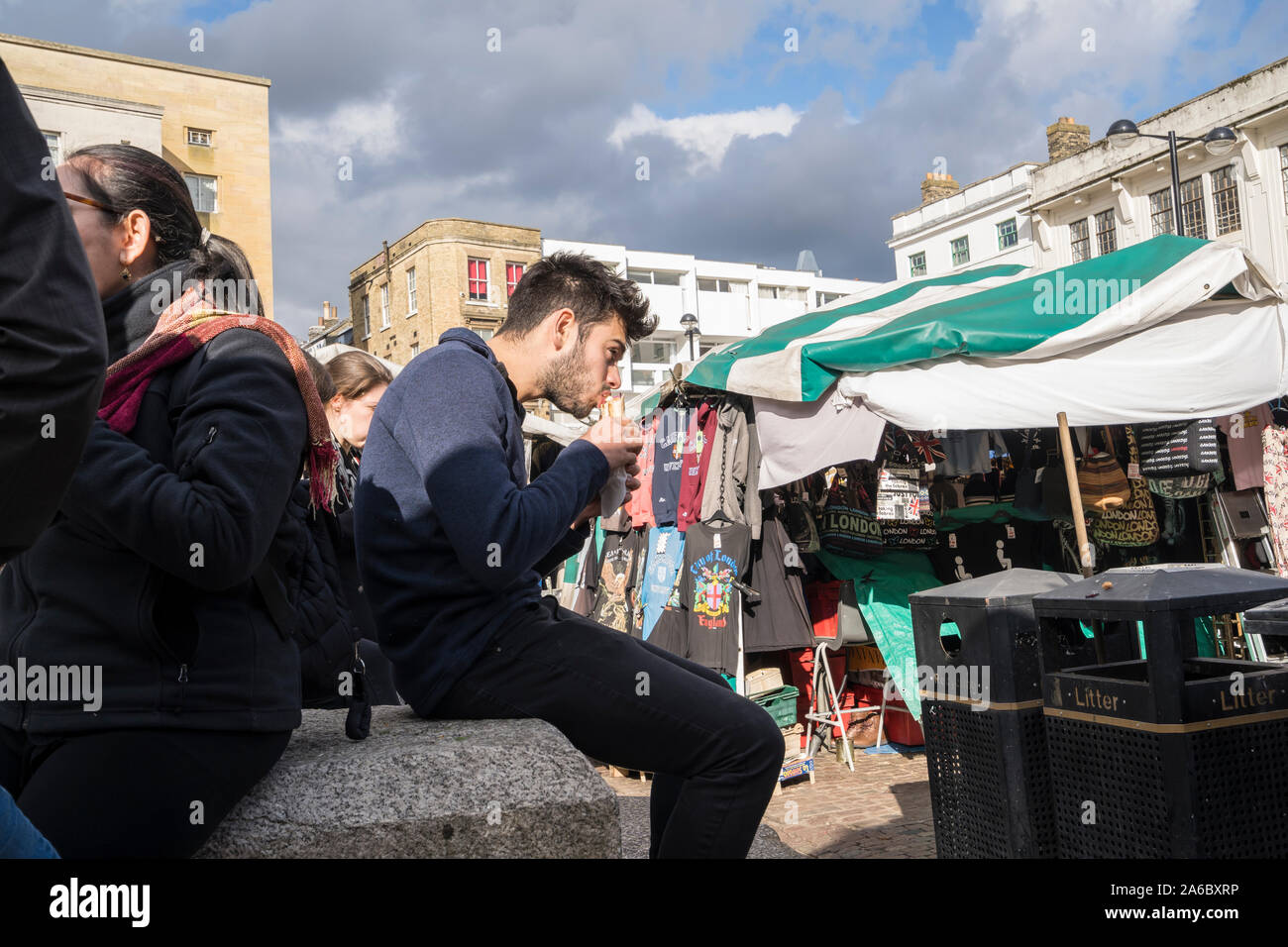 Young man eating filled bread roll in market hill Cambridge 2019 Stock Photo