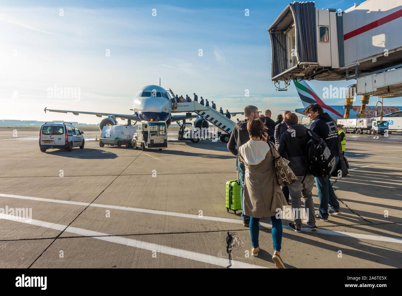 passengers-use-steps-to-board-a-british-airways-plane-heathrow-airport-2A6TE5X.jpg