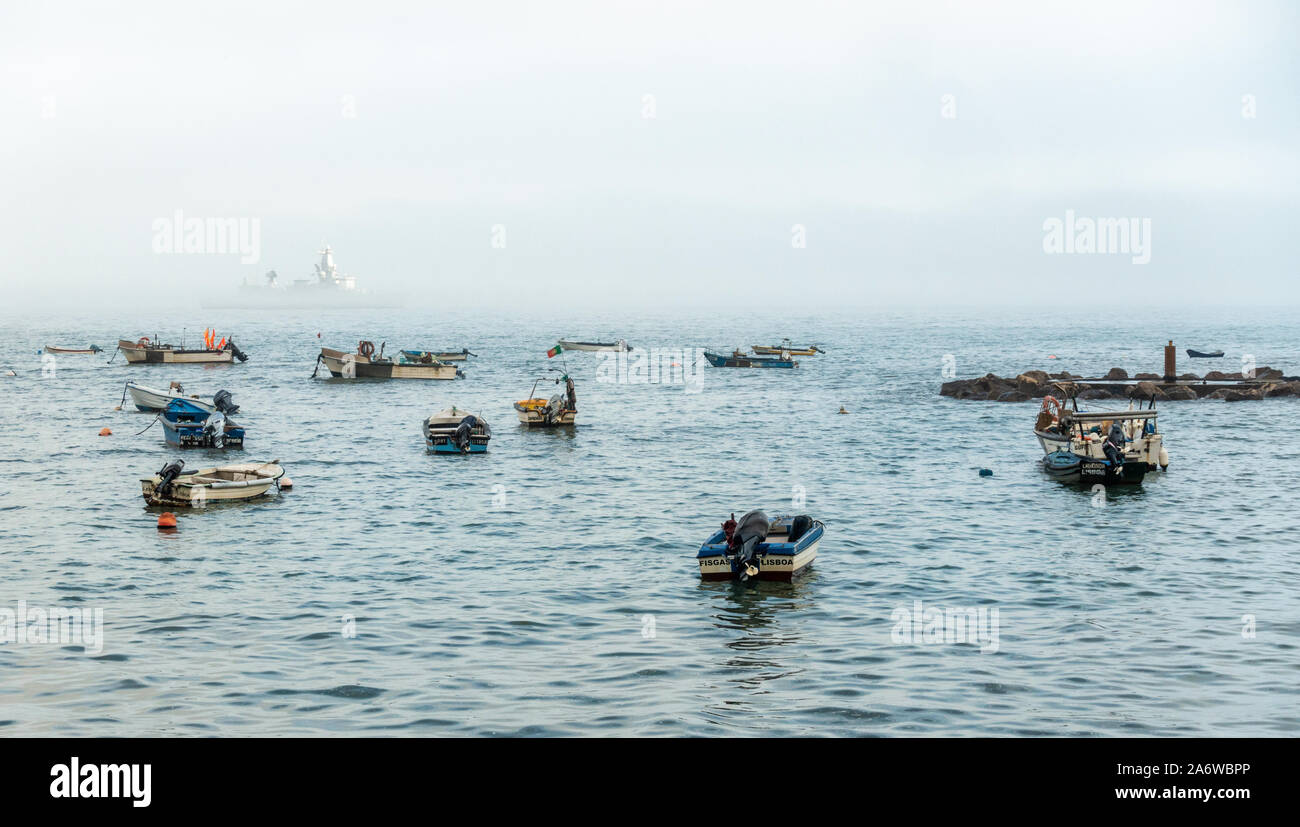 a-large-ship-is-just-visible-through-the-mist-as-smaller-boats-are-moored-in-the-foreground-2A6WBPP.jpg
