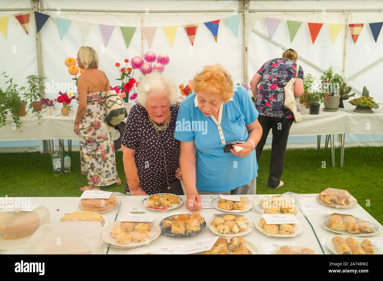 Two ladies inspect the scones in the flower tent Stock Photo