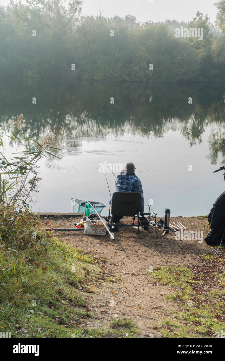 Angler fishing on a cold misty autumn day Milton Park 2019 Stock Photo