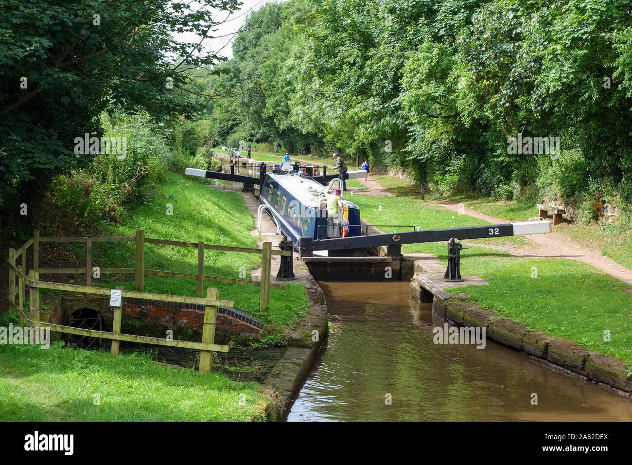 a-canal-boat-or-barge-passing-through-meaford-house-lock-on-the-trent-and-mersey-canal-at-meaford-near-stone-staffordshire-england-uk-2A82DEX.jpg