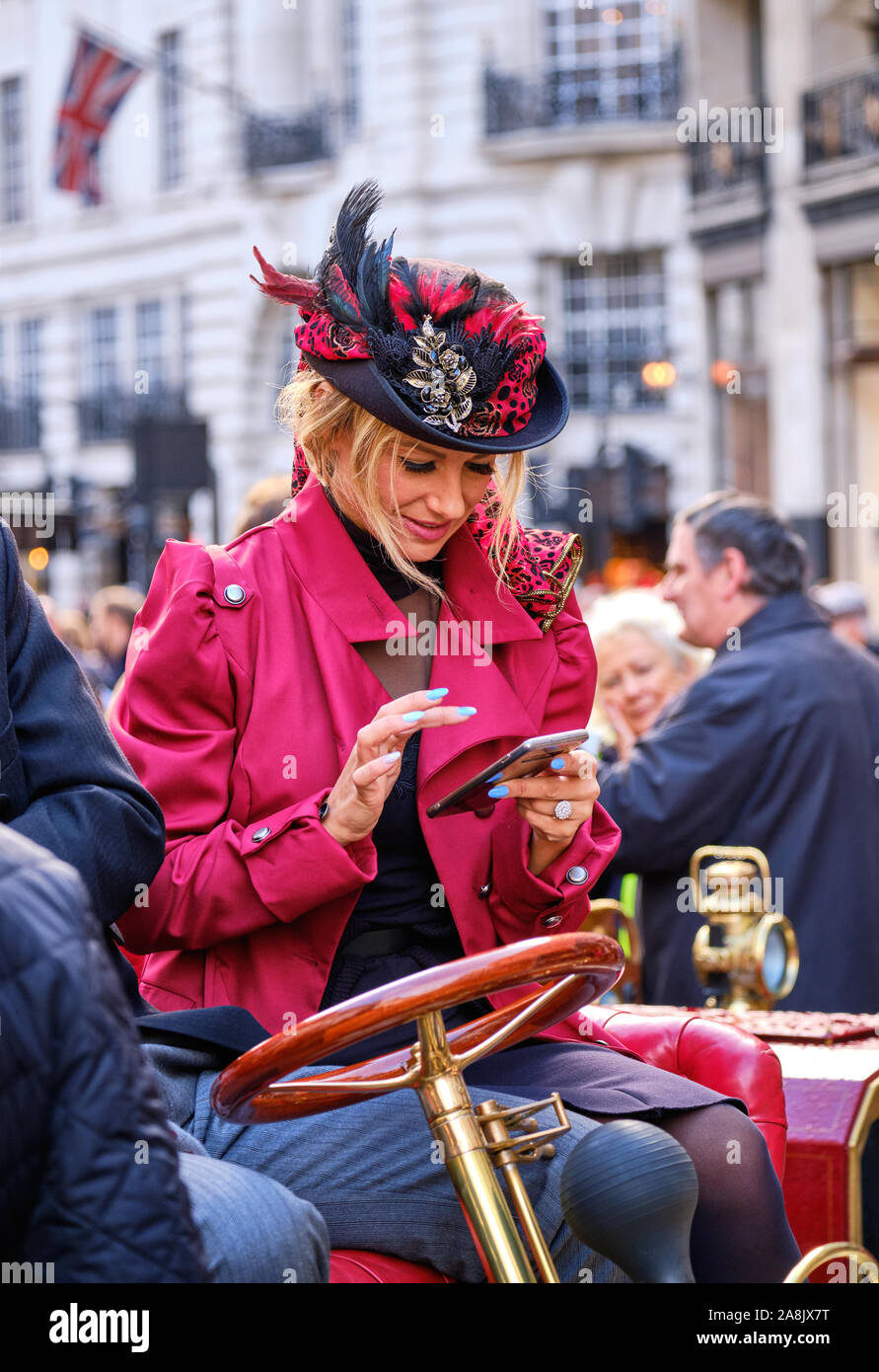young-lady-in-vintage-victorian-clothing-sitting-on-vintage-car-looking-at-her-cell-phone-creating-an-anachronism-2A8JX7T.jpg