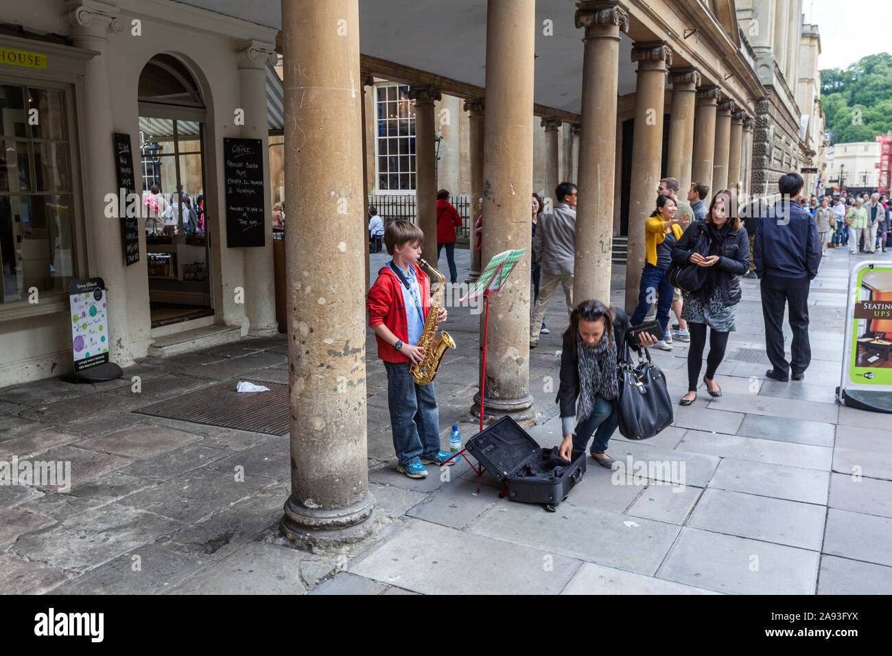 woman-giving-money-to-a-young-boy-busker