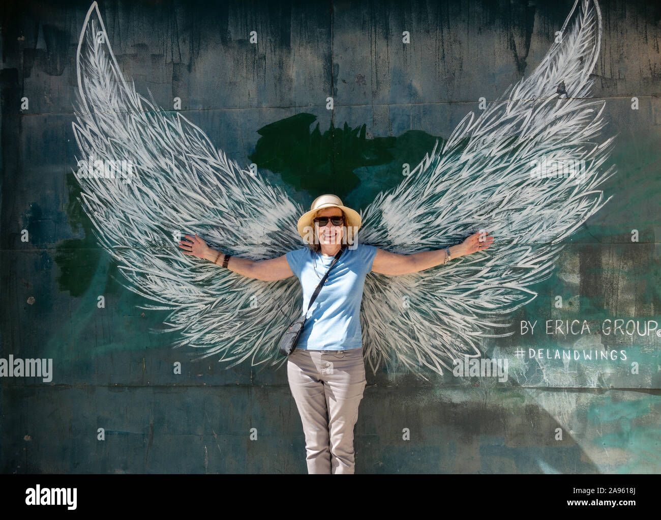 Mature Retired Woman Posing In Front Of The DeLand Wings Mural Painted By The Erica Group Stock Photo