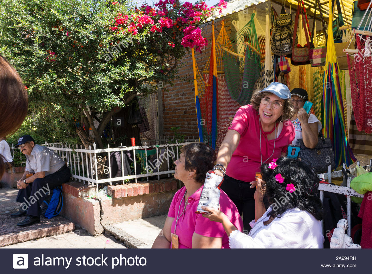 Women watching a performance at Xochimilco, Mexico City, with market goods in the background. Stock Photo