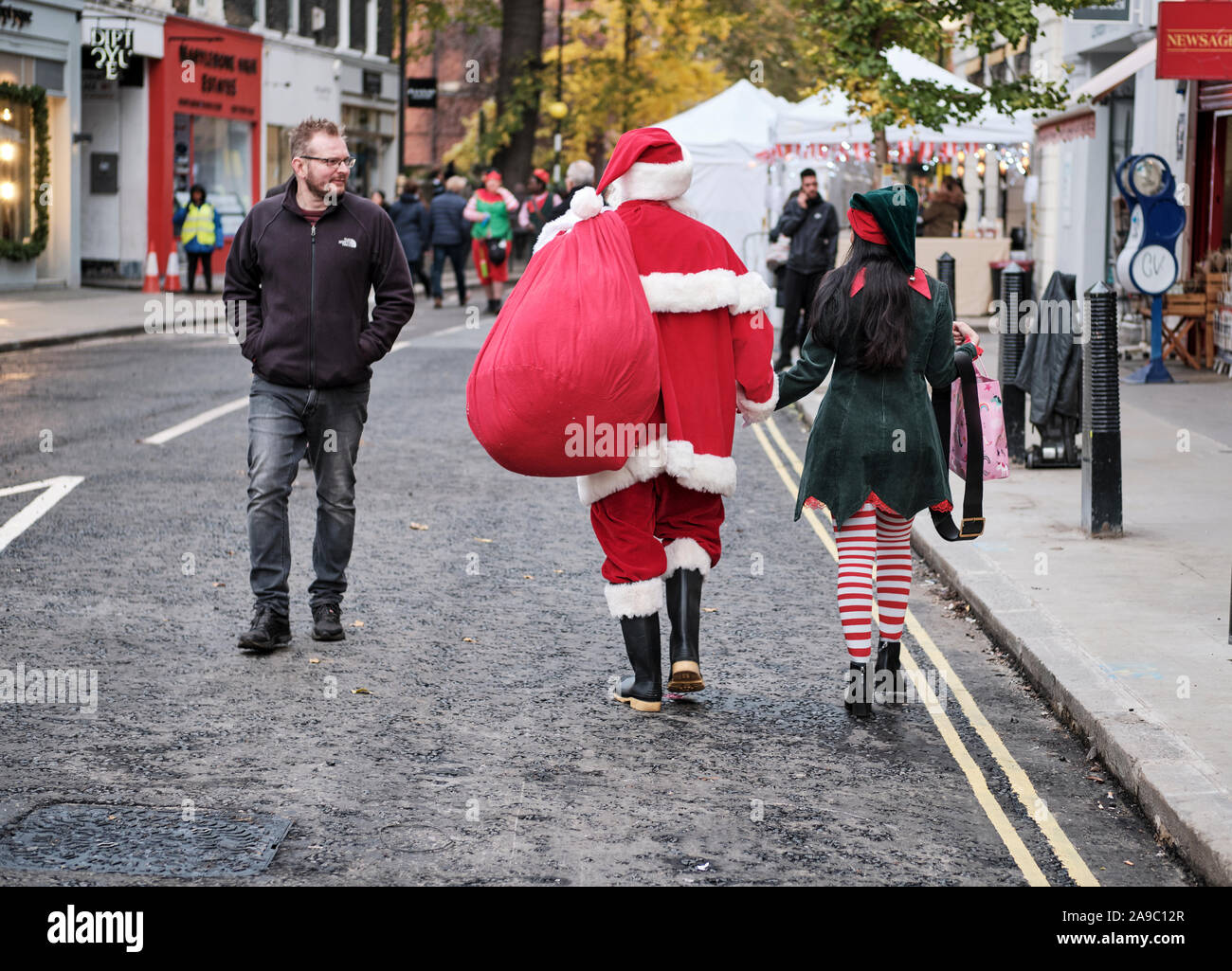santa-claus-and-an-elf-walking-away-hand-in-hand-getting-look-from-passer-by-on-london-street-2A9C12R.jpg