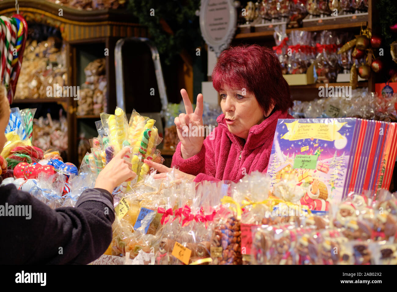 lady-food-vendor-in-a-candy-shop-showing-price-two-fingers-of-the-sweet-treats-to-a-faceless-customer-at-the-strasbourg-christmas-market-2AB02X2.jpg
