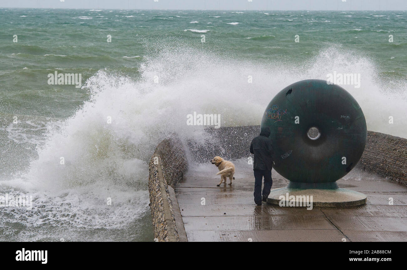 Brighton UK 26th November 2019 - A walker and his dog  gets a soaking by waves crashing in on Brighton seafront as the remnants of Tropical Storm Sebastien arrive in Britain bringing strong winds and rain to most parts of the country . Credit: Simon Dack / Alamy Live News Stock Photo