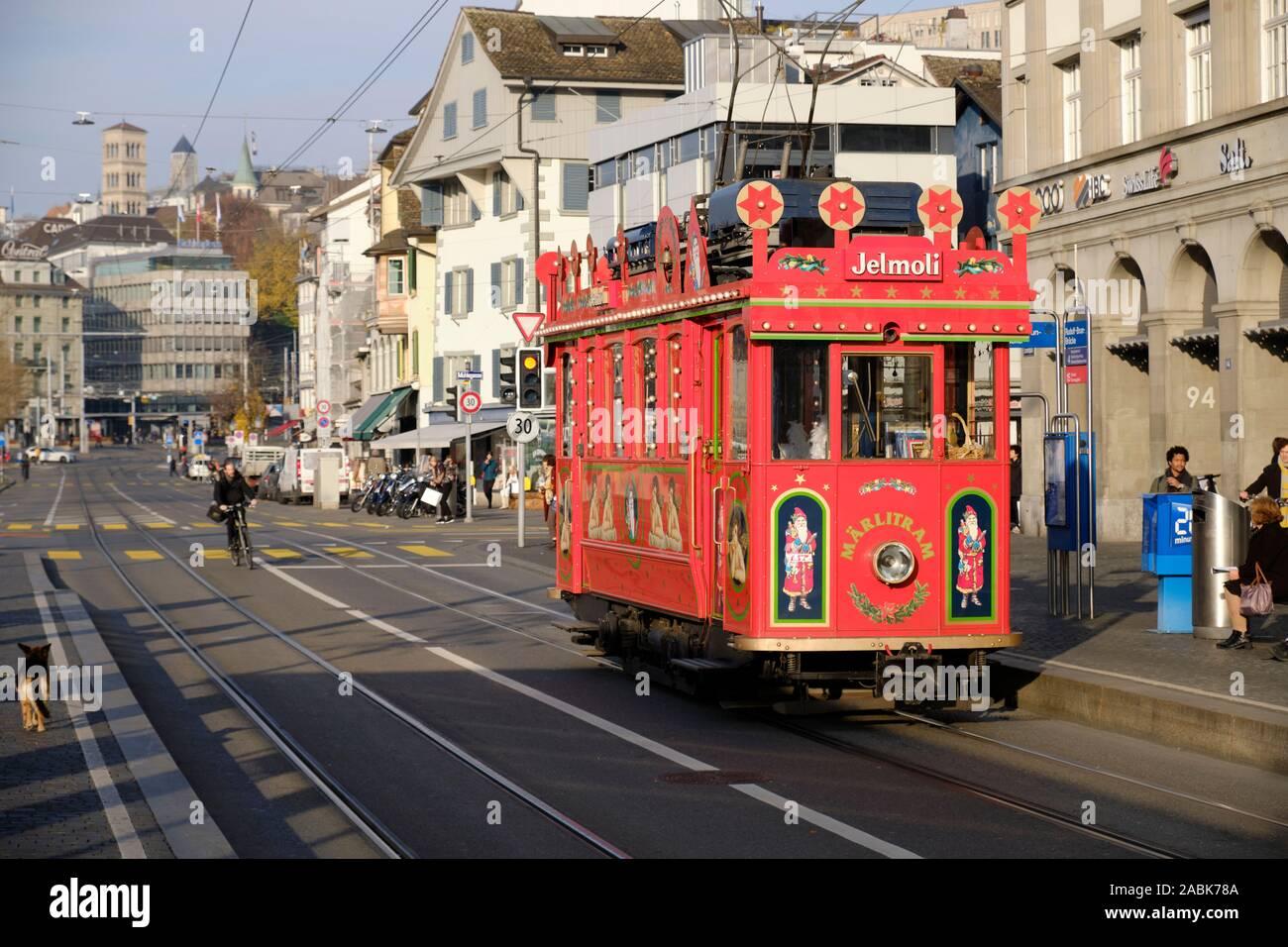 the-marlitram-streetcar-a-christmas-festive-tram-going-along-on-the-sun-lit-street-along-the-river-side-of-zurich-switzerland-2ABK78A.jpg