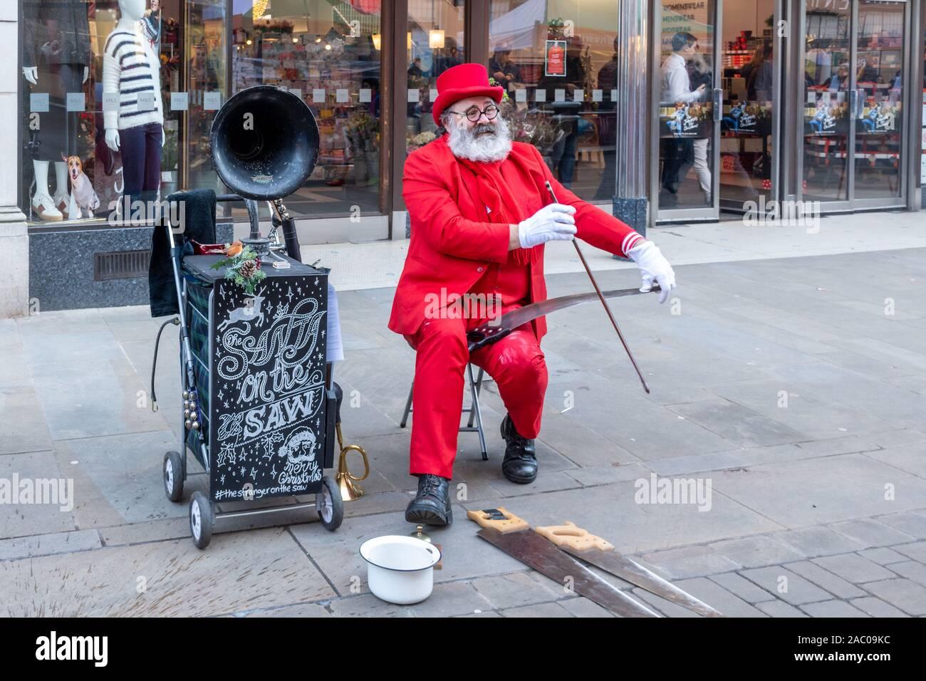 santa-on-the-saw-musician-busker-on-high-street-christmas-entertainment-uk-2AC09KC.jpg