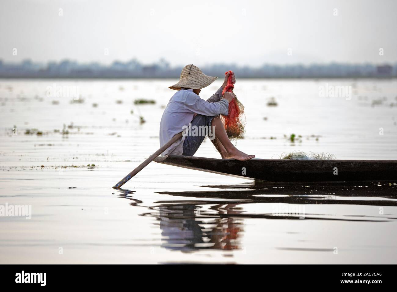 person-preparing-a-net-for-fishing-on-inle-lake-myanmar-burma-2AC7CA6.jpg