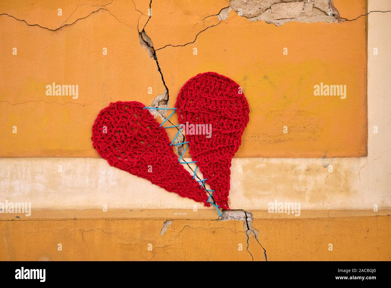 concrete-wall-with-a-crack-covered-by-a-wool-knitting-of-two-parts-of-heart-held-together-by-a-single-string-2ACBGJ0.jpg