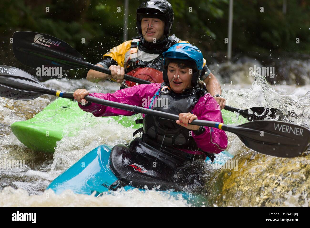 Female and male kayakers shooting the rapids at the National White Water Centre on the River Tryweryn in Snowdonia National Park Stock Photo