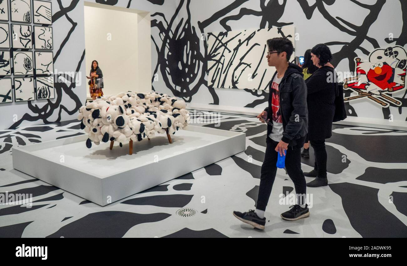 people-standing-by-art-by-brian-donnelly-aka-kaws-sculptor-and-graffiti-artist-exhibition-at-national-gallery-of-victoria-ngv-melbourne-australia-2ADWK95.jpg