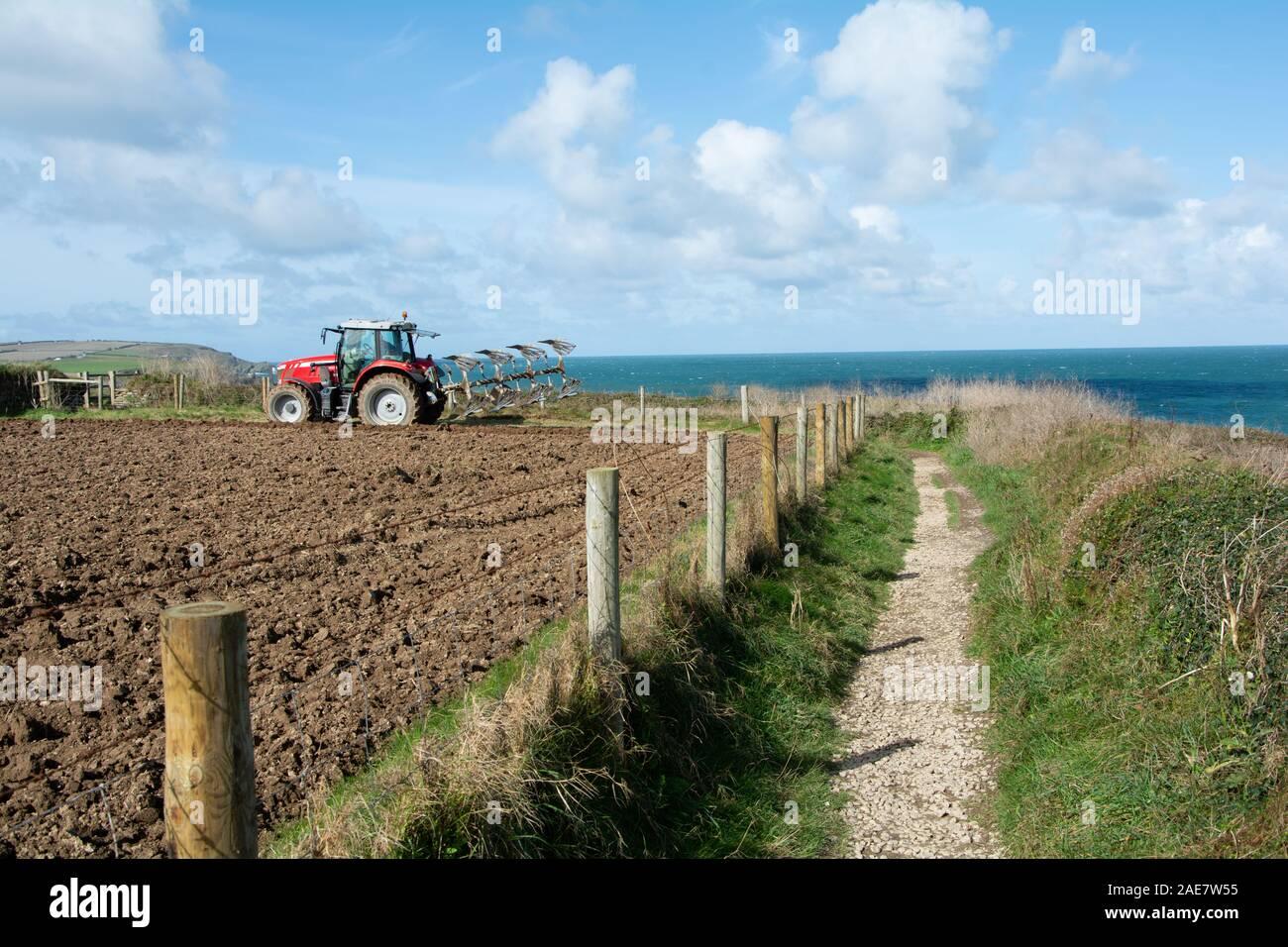 October 2019 - A farmer ploughs his field on a coastal farm in Trevose Head,Cornwall, UK Stock Photo