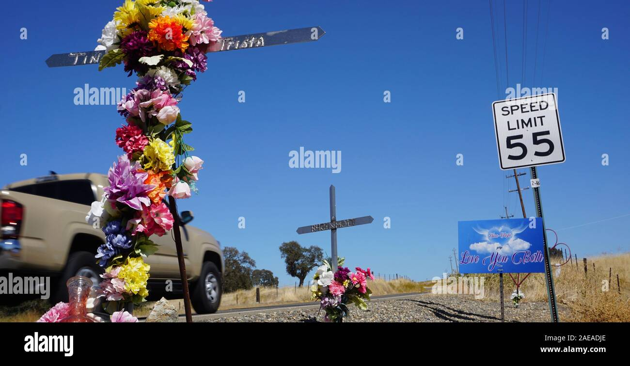 Roadside car accident memorials with flowers and speed limit sign with pickup truck driving by in Tuolumne County, California. Stock Photo