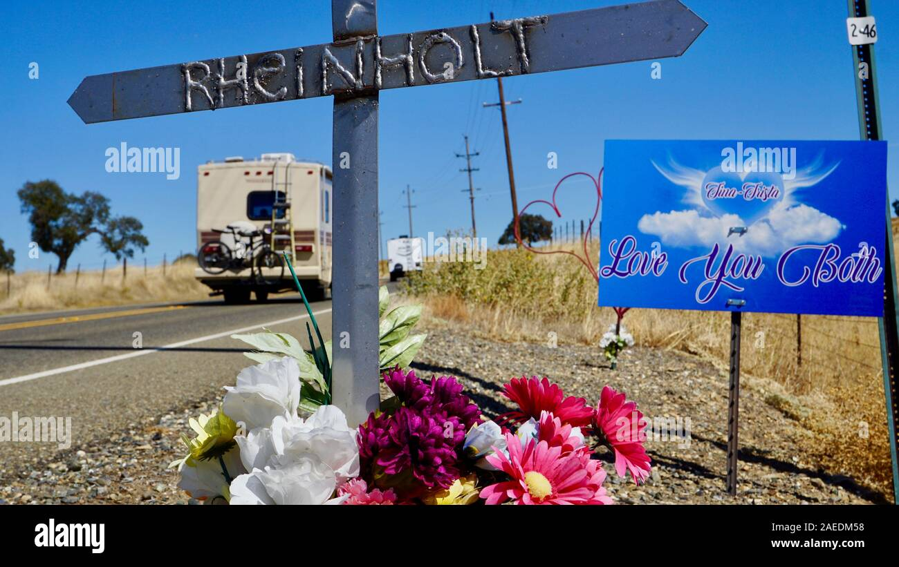 Roadside car accident memorial with a metal cross with the name Rheinholt, with recreational vehicles driving by in Tuolumne County, California. Stock Photo