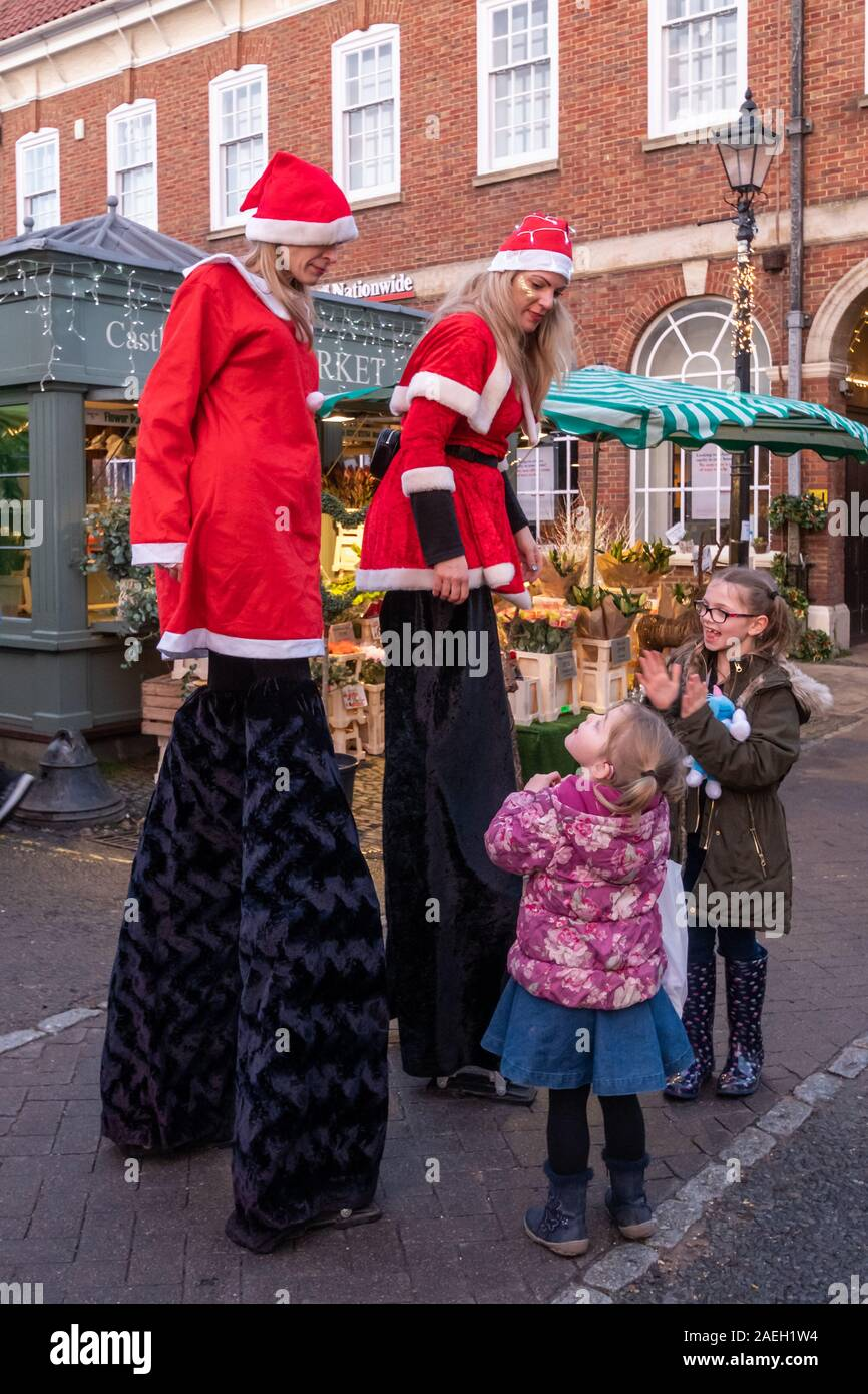 stilt-walkers-dressed-in-santa-costumes-at-the-farnham-christmas-market-2019-in-the-town-centre-surrey-uk-2AEH1W4.jpg