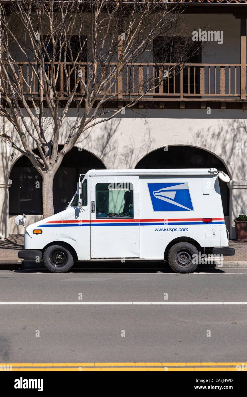 USPS delivery truck parked outside house Stock Photo