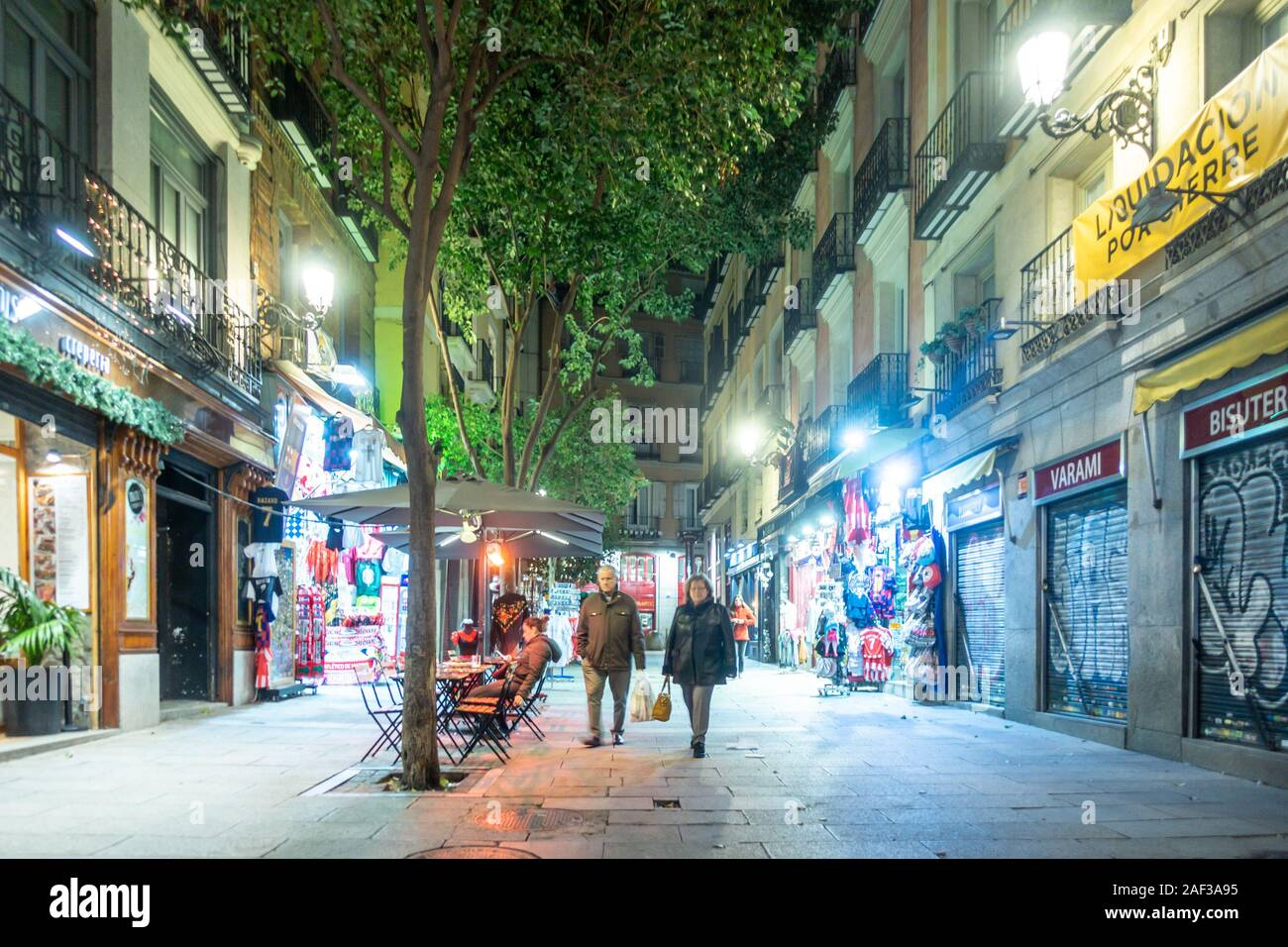 a-view-down-a-city-centre-street-called-calle-de-postas-in-madrid-spain-at-night-trees-run-down-the-middle-of-the-street-which-is-lit-up-by-lights-2AF3A95.jpg
