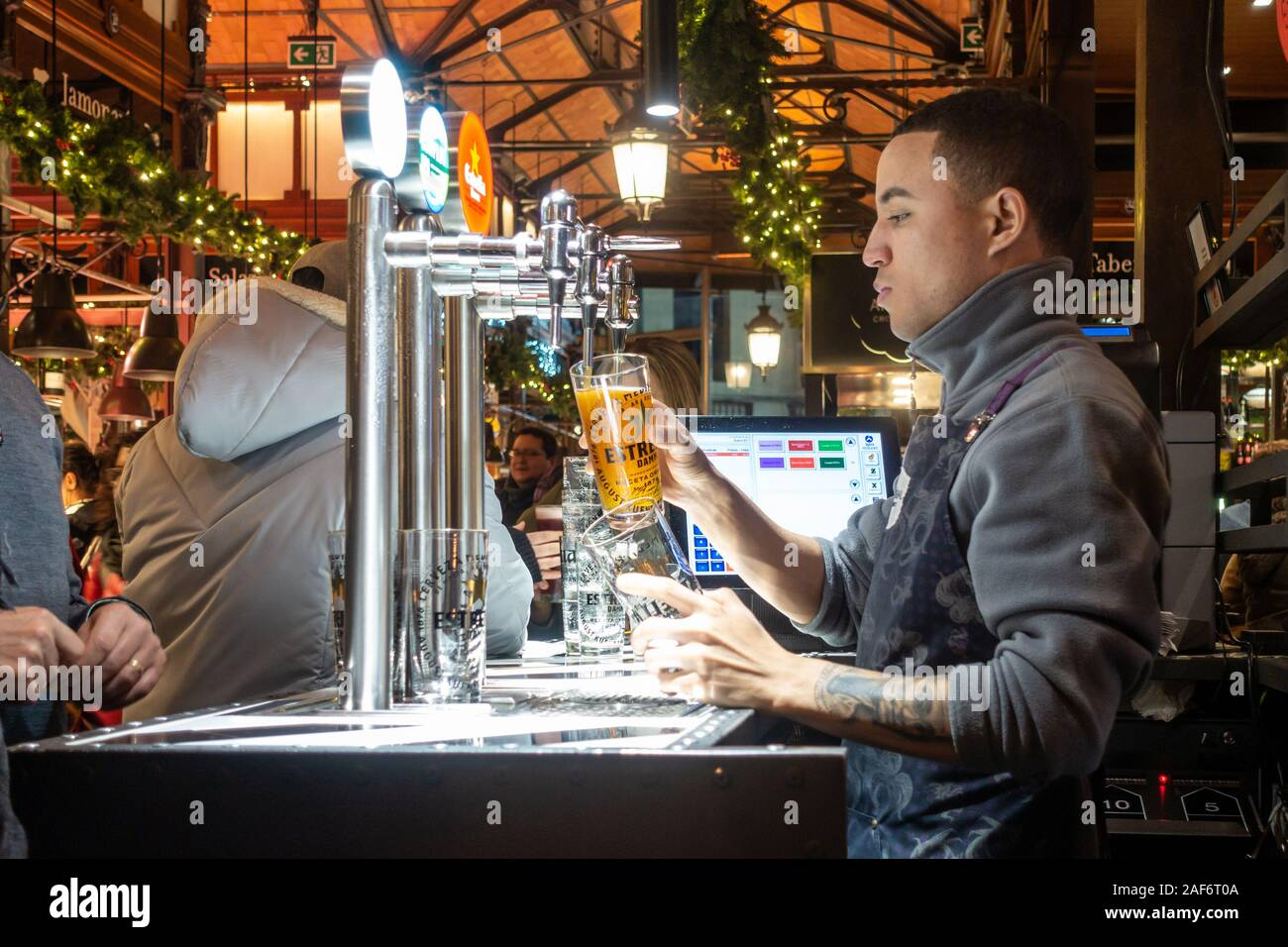 a-barman-pours-a-beer-for-a-customer-in-mercado-san-miguel-an-indoor-market-in-madrid-spain-seen-here-on-the-evening-close-to-christmas-2AF6T0A.jpg