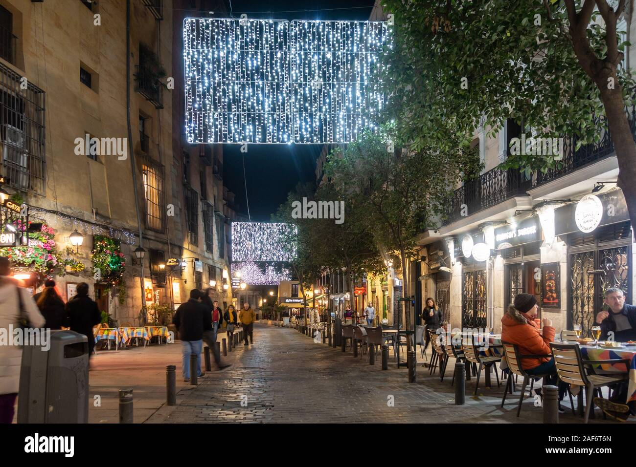 people-sat-outside-at-tables-in-cava-de-san-miguel-in-madrid-spain-it-is-december-close-to-christmas-and-decorations-adorn-the-streets-2AF6T6N.jpg