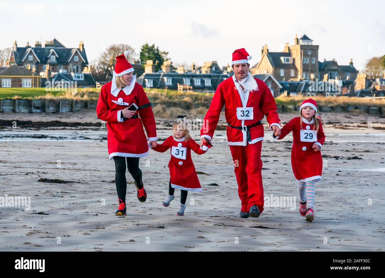 parents-children-in-santa-costumes-runni