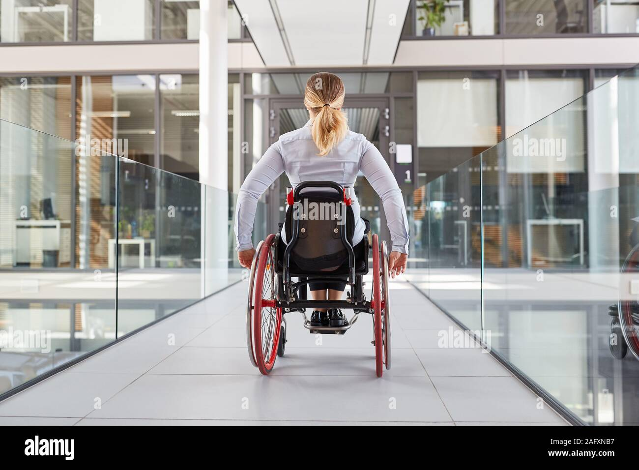 Paralyzed woman in a wheelchair on the move in the disabled office building Stock Photo