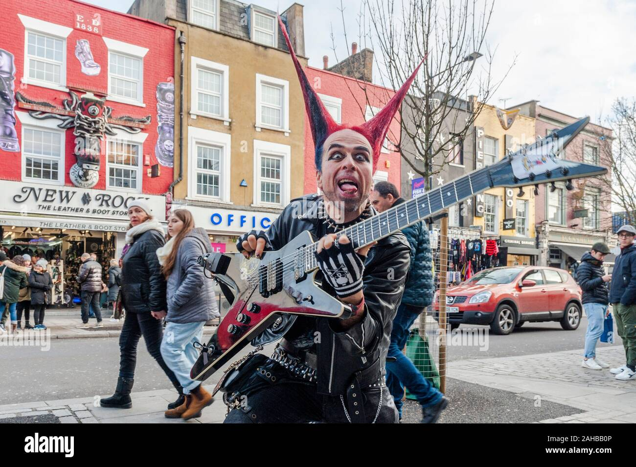 man-dressed-in-punk-rocker-clothes-with-spiked-hair-and-a-guitar-poses-for-tourist-pictures-on-camden-high-street-camden-london-uk-2AHBB0P.jpg