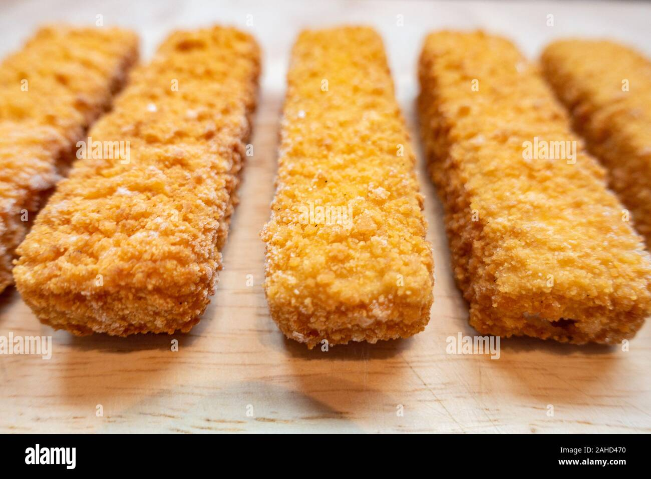 close-up-view-of-fish-fingers-on-a-wooden-chopping-board-2AHD470.jpg